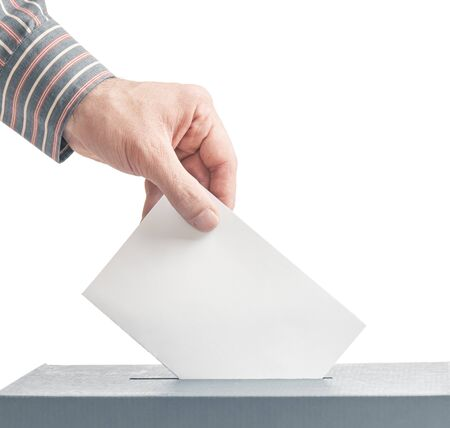 Elections. Male hand putting a ballot into a voting box isolated on a white background. Copy-space. Stok Fotoğraf