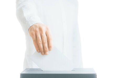 Elections. Unrecognizable man in a shirt putting a ballot into a voting box isolated on a white background. Copy-space.