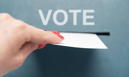 Woman putting a ballot list into a voting box, point of view in first person. Elections.