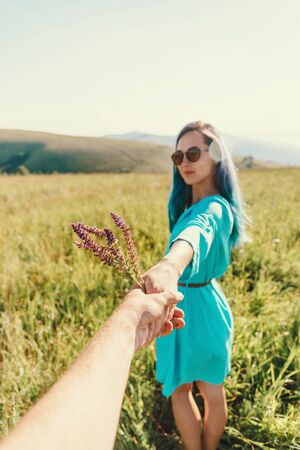 Couple in love. Beautiful young woman in blue dress holding male hand with bouquet of wildflowers and leading him in summer green grass meadow. Point of view shot.