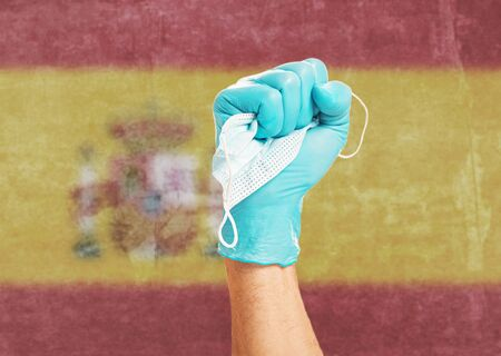 Fist hand gesture in medical protective glove with a mask on background flag of the Spain. Concept of stop virus disease. Stok Fotoğraf