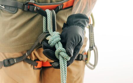 Unrecognizable sporty man climber in safety harness holding rope knot eight indoor, close-up.