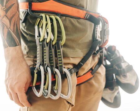Unrecognizable sporty man in safety harness with climbing equipment and shoes on a white background.