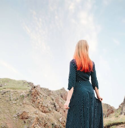 Unrecognizable red-haired young woman wearing in long dress walking on nature outdoor.