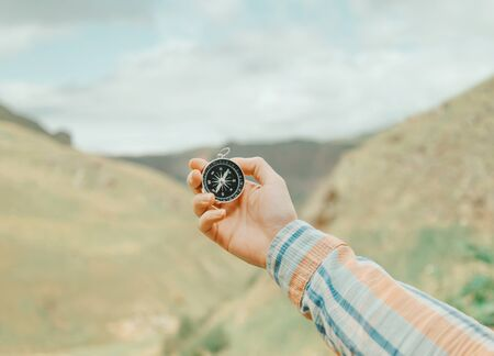 Hiker young woman holding magnetic compass in a hand and searching direction in summer mountains valley, point of view. Stok Fotoğraf