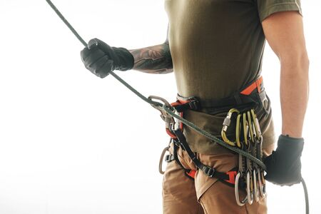 Sporty climber man in safety harness belaying with rope and figure eight indoor on a white background. Standard-Bild