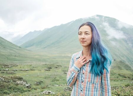 Beautiful blue and violet hair young woman in a plaid shirt walking in summer mountains.