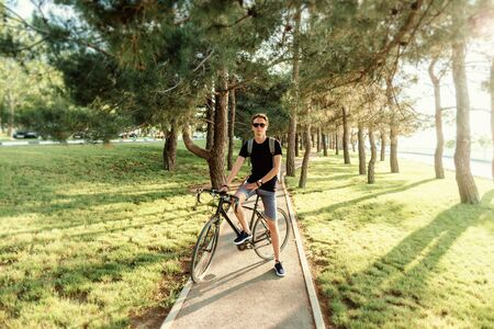 Casual style young man in sunglasses standing with bicycle on path in pine woods summer park.