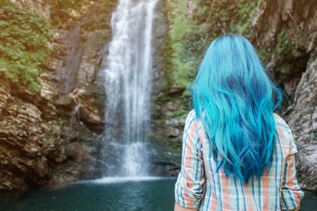 Rear view of young woman with blue hair looking at waterfall in summer.