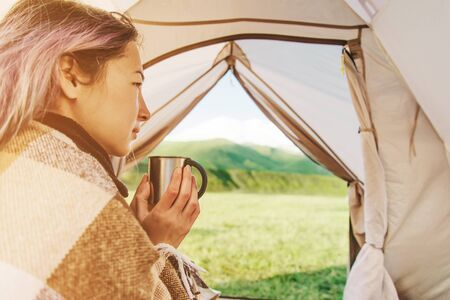 Young woman wrapped in plaid resting with a cup of tea in a tent and looking at mountain landscape. View from inside.