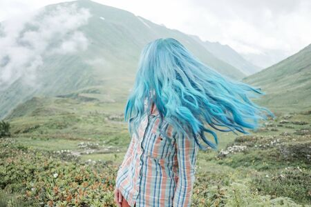 Beautiful blue hair young woman in plaid shirt relaxing in summer mountains outdoor.