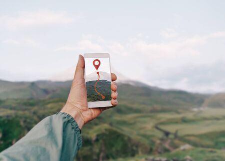 Traveler hiker man holding smartphone in a hand and using GPS app with trekking in summer mountains outdoor. Point of view in first person. Stok Fotoğraf