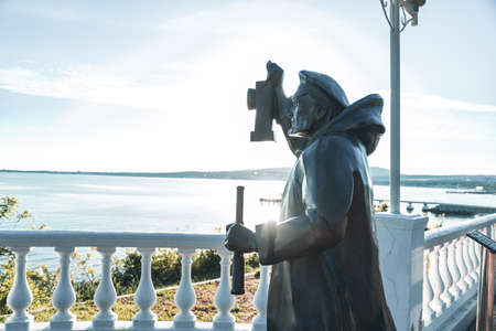 """Gelendzhik, Russia, 27 May 2020: Sculpture """"Old light keeper"""" on embankment on background of Black sea bay in summer. Editorial"""
