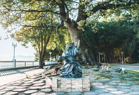 """Gelendzhik, Russia, 27 May 2020: Sculpture """"Cat the Scientist"""" near oak tree on embankment of Black sea in summer. Monument was created based on the works of A. S. Pushkin."""