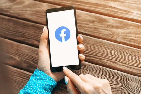 Gelendzhik, Russia, 19 November 2019: Woman hands holding smartphone and using Facebook app at wooden table, point of view in first person. Editöryel