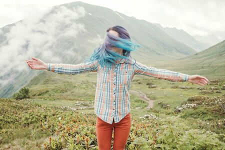 Happy and freedom traveler young woman with blue hair relaxing in summer mountains.