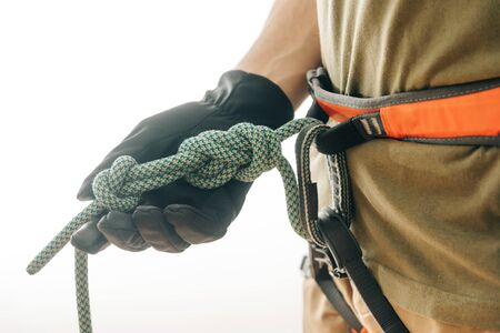 Unrecognizable sporty man climber in safety harness and gloves holding rope knot eight indoor, close-up.