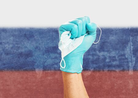Doctor fist hand in protective glove holding a mask on background flag of the Russia. Concept of stop covid-19 virus. Stok Fotoğraf