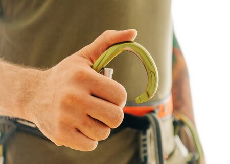 Close-up of climber sporty man hand with snap hook carabiner.