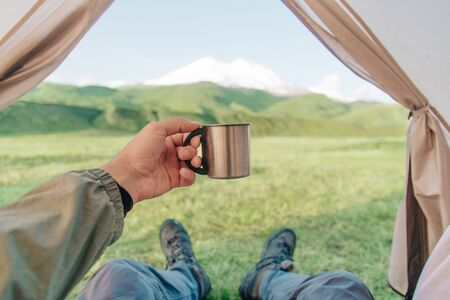 Hiker traveler young man resting in a tent with cup of tea and enjoying view of mountain Elbrus with snowy peaks, point of view in first person. Stok Fotoğraf