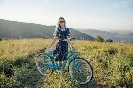 Beautiful young woman in dress standing with bicycle cruiser on rural road along green summer meadows and looking at camera.