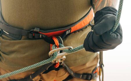 Unrecognizable sporty climber man in safety harness and gloves belaying with rope and figure eight device indoor, close-up.