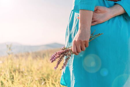 Unrecognizable woman relaxing with bouquet of wildflowers in summer green grass meadow. Stok Fotoğraf