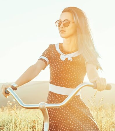 Beautiful young woman in dress and sunglasses riding bicycle on sunny summer day outdoor.