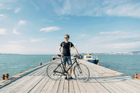 Casual style handsome guy standing with bicycle on a wooden pier of sea on sunny summer day.