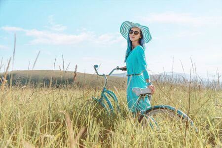 Beautiful romantic young woman in dress and hat walking with bicycle in summer green grass field.