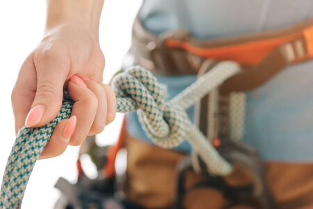 Unrecognizable sporty woman in climbing and mountaineering harness holding rope, close-up.
