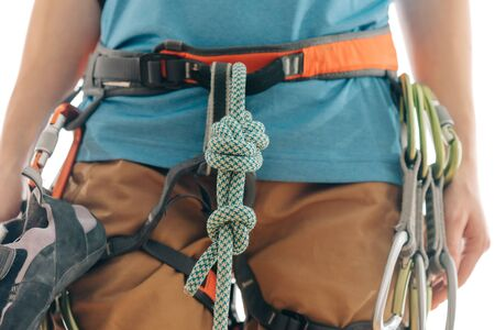 Unrecognizable sporty woman in safety harness with climbing and mountaineering equipment, close-up front view.