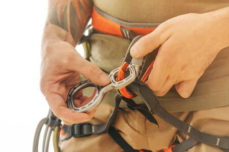 Unrecognizable climber man in safety harness attaches a figure of eight device to carabiner, close-up.