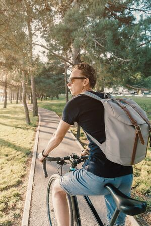 Young man casual stylish with backpack riding on bicycle in green summer city park. Stok Fotoğraf