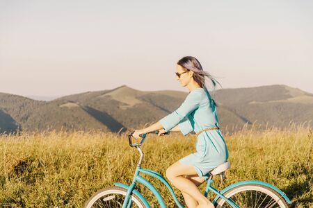 Happy freedom beautiful young woman in blue dress riding bicycle in summer green grass meadow in front of mountain ridge.