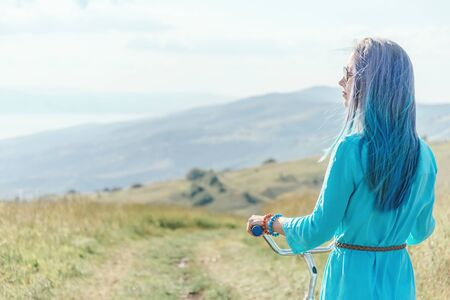 Beautiful girl with blue hair walking with bicycle in summer nature outdoor.