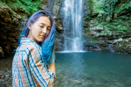 Blue hair smiling young woman resting near the waterfall in summer.