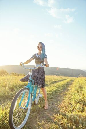 Beautiful young woman in dress riding bicycle cruiser on countryside path along green summer meadows.