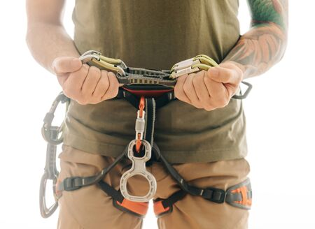 Unrecognizable sporty man in safety harness with climbing equipment holding set of quickdraws indoor on a white background. Stok Fotoğraf