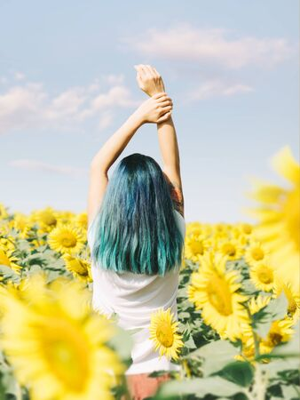 Rear view of happy girl with blue hair relaxing with hands up in blooming sunflowers field on sunny summer day.