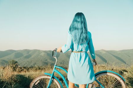 Stylish woman with blue hair standing with bicycle in front of mountain ridge in summer outdoor, rear view.