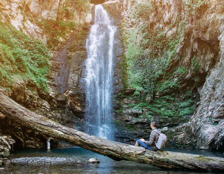 Explorer young man with backpack resting on fallen tree trunk and enjoying view of waterfall in summer.
