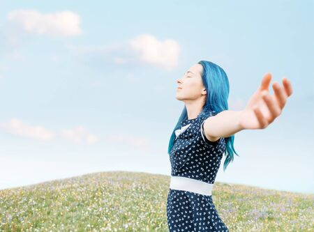 Happy blue hair young woman in dress relaxing with raised arms in summer meadow, side view.