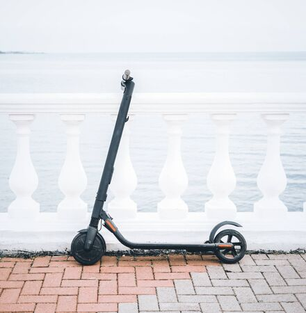 Ecological transport electric scooter on city embankment in front of sea in summer. No people.