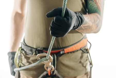 Sporty climber man in safety harness belaying with rope and figure eight device indoor, front view.