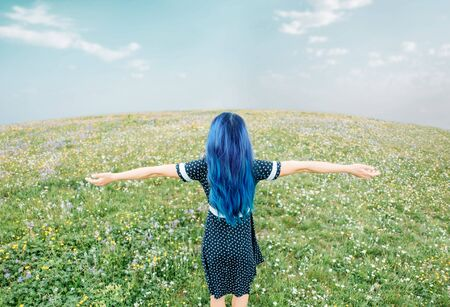 Blue hair young woman in dress resting with raised arms in summer meadow, rear view.