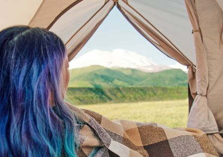 Blue hair young woman wrapped in plaid resting in a tent and enjoying of mountain landscape. View from inside.