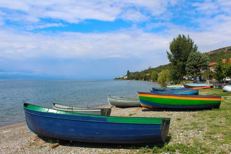 several wooden colorful boats on the beach against the blue sky, macedonia, Balkans