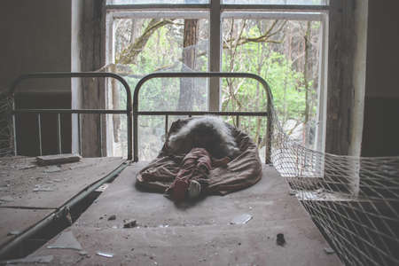 Old doll infected with radiation. Abandoned building in Pripyat. Interior of an abandoned house