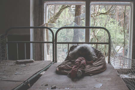 Old doll infected with radiation is lying on the bed. Abandoned building in Pripyat